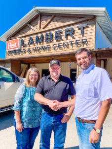 Chris Miller from Nation's Best shakes hands with owners of Lambert Lumber & Home Center
